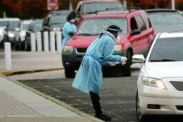 Day Street Community Health Center staff conduct drive-thru coronavirus testing Wednesday, Octoer 28, 2020, at Brien McMahon High School in Norwalk, Conn.