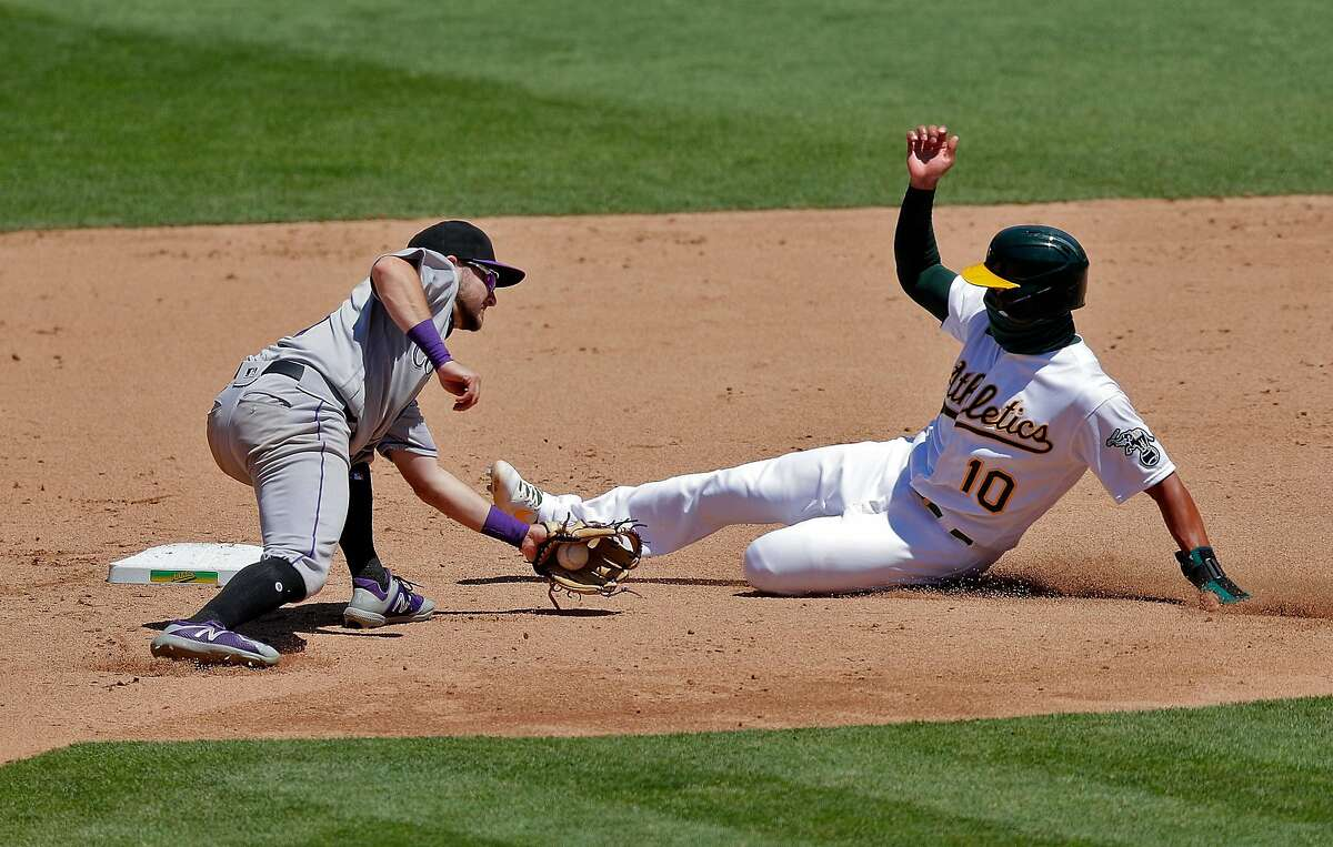 Trevor Story (27) goes to apply the tag to Marcus Semien (10) who broke for second but Ramon Laurieano (22) had struck out looking on the play in the fifth as the Oakland Athletics played the Colorado Rockies at the Coliseum in Oakland, Calif., on Wednesday, July 29, 2020.