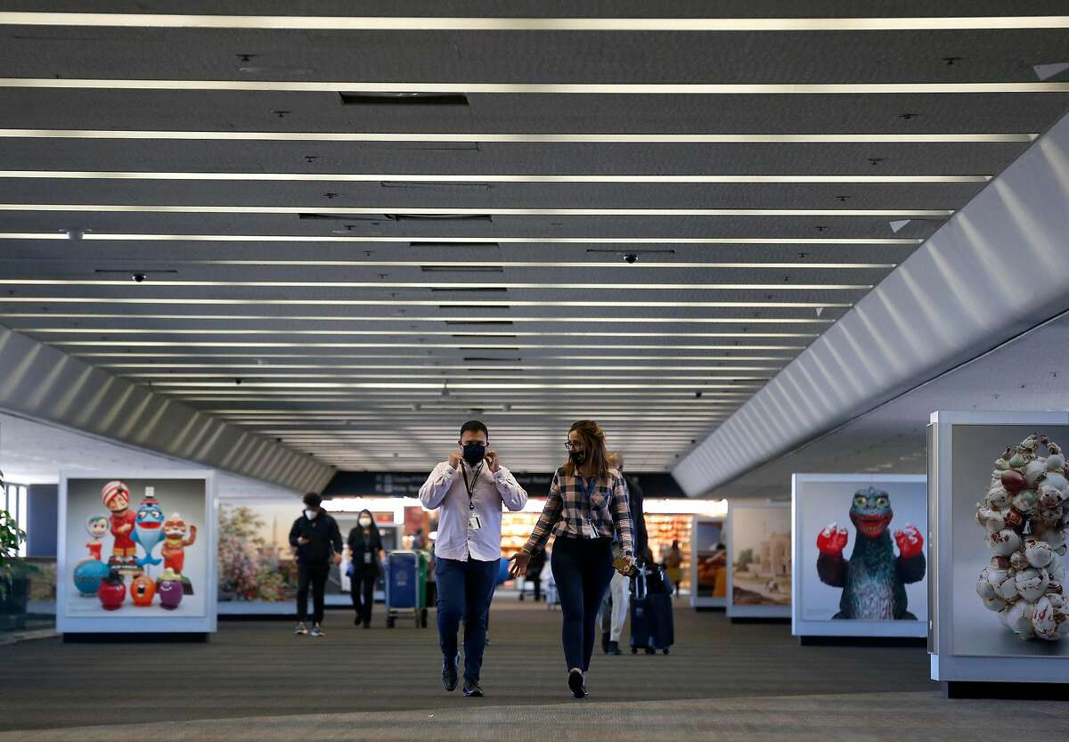 Airport employees and passengers walk through an uncrowded Terminal 3 at SFO in San Francisco, Calif. on Thursday, Oct. 15, 2020. As the airline industry sees a modest rise in travel, a rapid COVID-19 testing site has been set up at the airport to provide travelers with documentation of test results to present upon arrival at their final destinations.