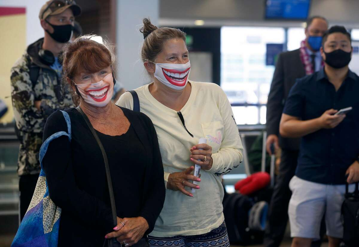 Michelle Fehr (left) and Susanne Bartley are all smiles while waiting to board a United flight to Hawaii at SFO in San Francisco, Calif. on Thursday, Oct. 15, 2020. As the airline industry sees a modest rise in travel, a rapid COVID-19 testing site has been set up at the airport to provide travelers with documentation of test results to present upon arrival at their final destinations.