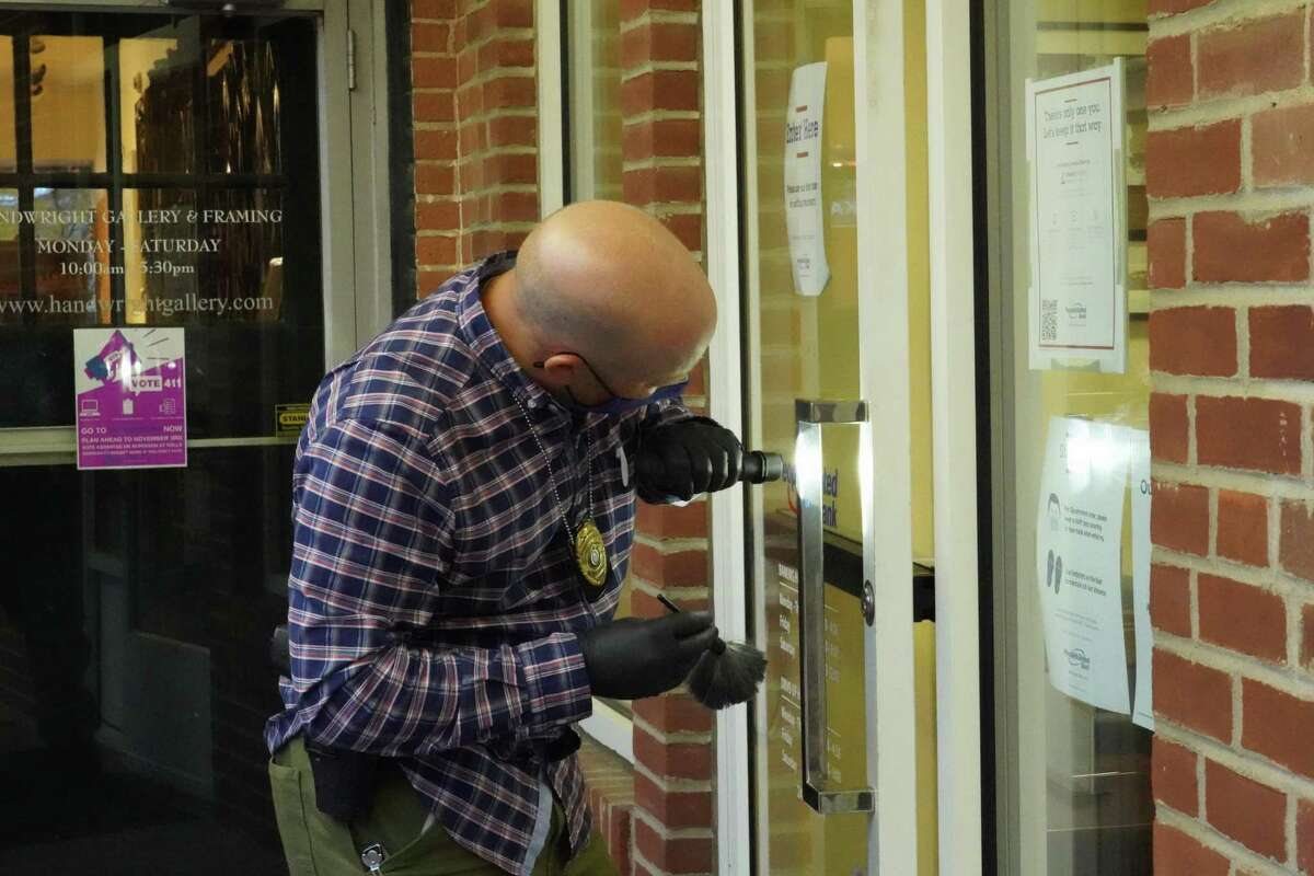New Canaan Police Sgt. Scott Romano dusts for fingerprints off the back door of People's United Bank at 95 Main St. in New Canaan after a holdup Wednesday, Oct. 28.