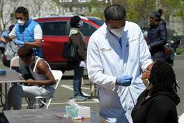 Dr. Fawad Hameedi of DOCS Urgent Care Stamford administers a COVID-19 nasal swab test on Lakeisha Thompson, 34, of Stamford at a walk up testing site for the coronavirus at AME Bethel Church in Stamford, Connecticut on May 2, 2020. The city is seeing a new spike in cases, Mayor Martin said Wednesday.