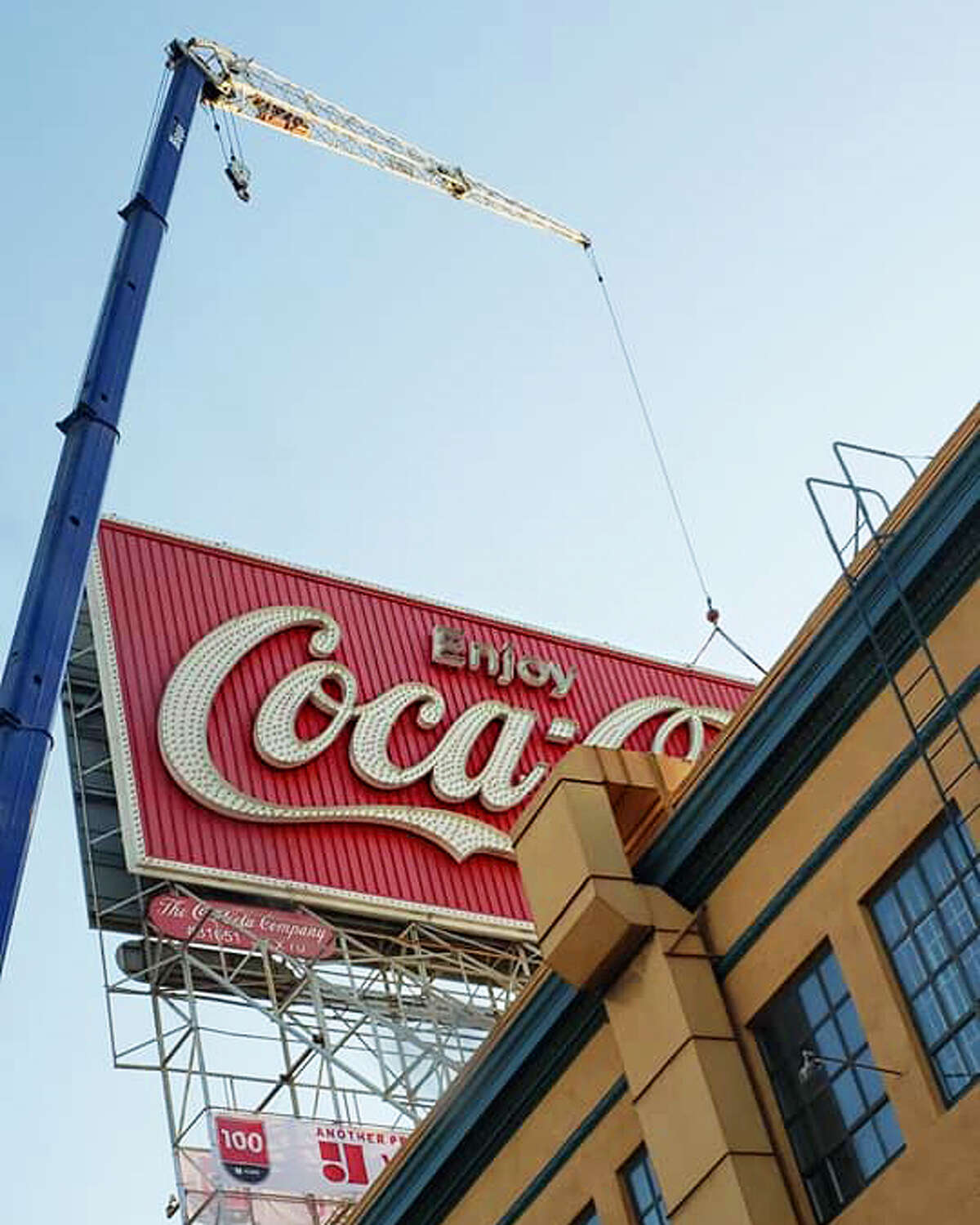 A crew takes down San Francisco's iconic Coca-Cola billboard in a photo posted Oct. 28, 2020.