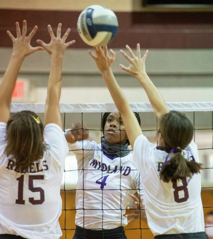 Midland High's Aniya Clinton looks to hit past Lee High's Ariana Franco and Emma Sanz 10/28/2020 at the Lee High gym. Tim Fischer/Reporter-Telegram Photo: Tim Fischer, Midland Reporter-Telegram