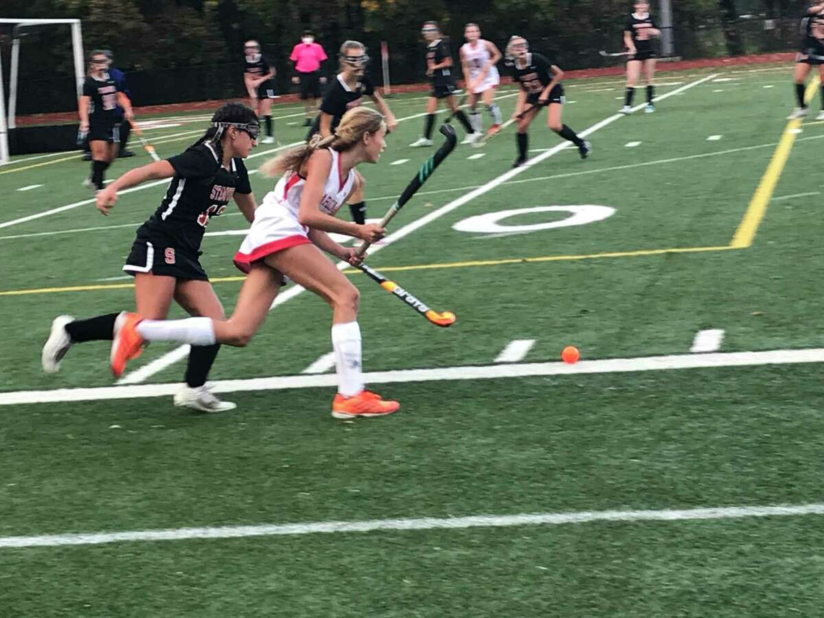 Klara Mueffelmann of Greenwich, right, moves the ball up the field, while being pursued in a field hockey game on October 28, 2020 in Greenwich, Connecticut.