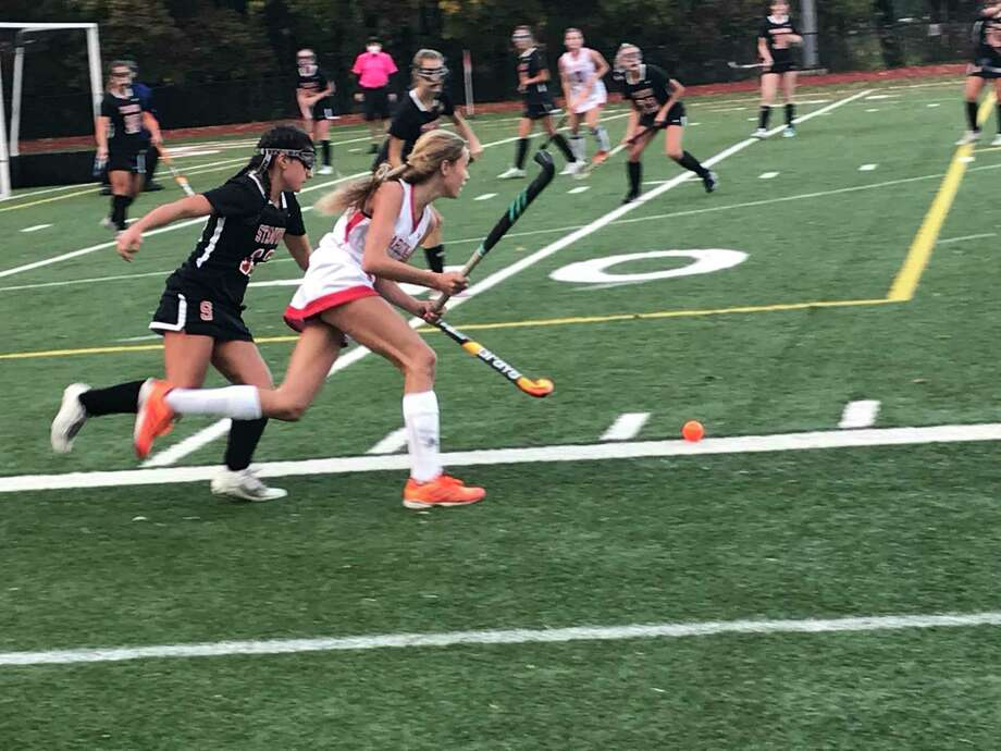 Klara Mueffelmann of Greenwich, right, moves the ball up the field, while being pursued in a field hockey game on October 28, 2020 in Greenwich, Connecticut. Photo: Contributed Photo