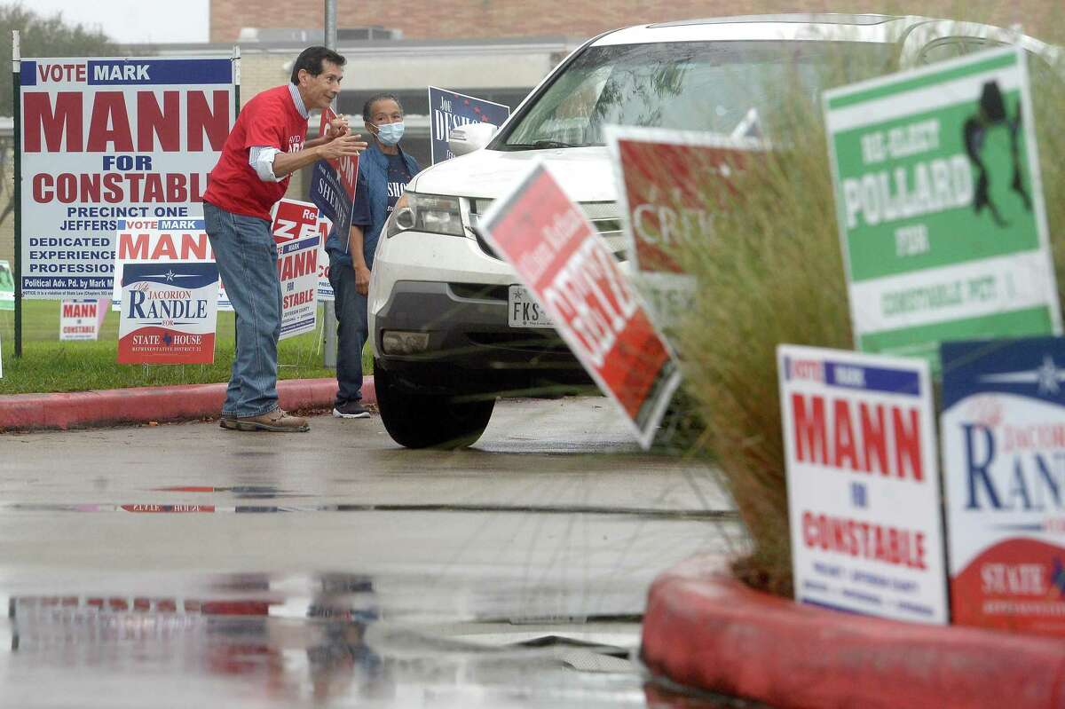 Campaigners greet cars making their way in to the Rogers Park poll site Wednesday morning. Crowds were sparse as rainfall began, settlinng in for the bulk of the day. Friday is the final day for early voting. Photo taken Wednesday, October 28, 2020 Kim Brent/The Enterprise