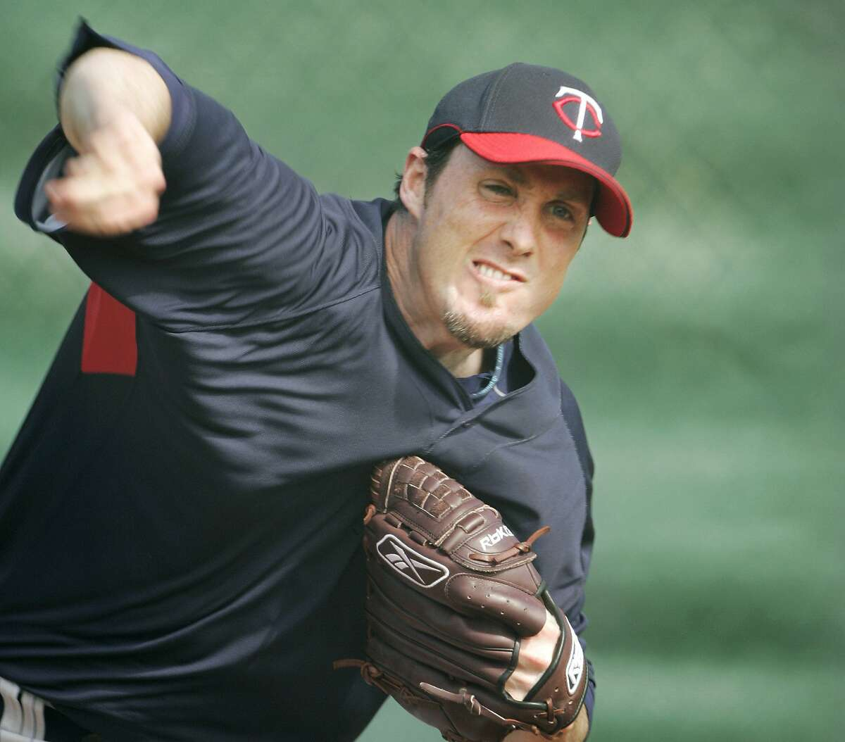 Minnesota Twins pitcher Joe Nathan follows through while working out in the bullpen at the teams baseball spring training facility, in Fort Myers, Fla., Wednesday, Feb. 20, 2008. (AP Photo/Steven Senne)