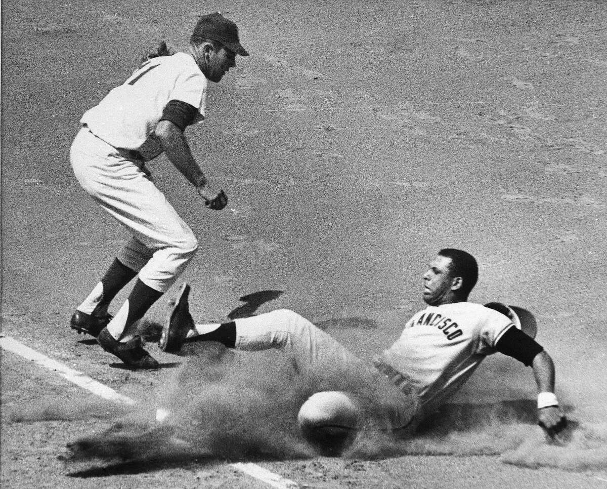 San Francisco Giants' first baseman Orlando Cepeda slides safely into third base as Los Angeles Dodgers' Ken McMullen covers the bag, Sept. 2, 1963.
