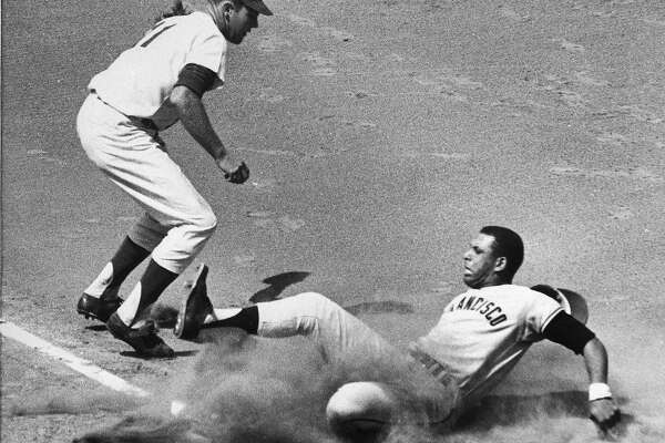 San Francisco Giants' first baseman Orlando Cepeda slides safely into third base as Los Angeles Dodgers' Ken McMullen covers the bag, Sept. 2, 1963. (AP Photo/Ed Widdis)