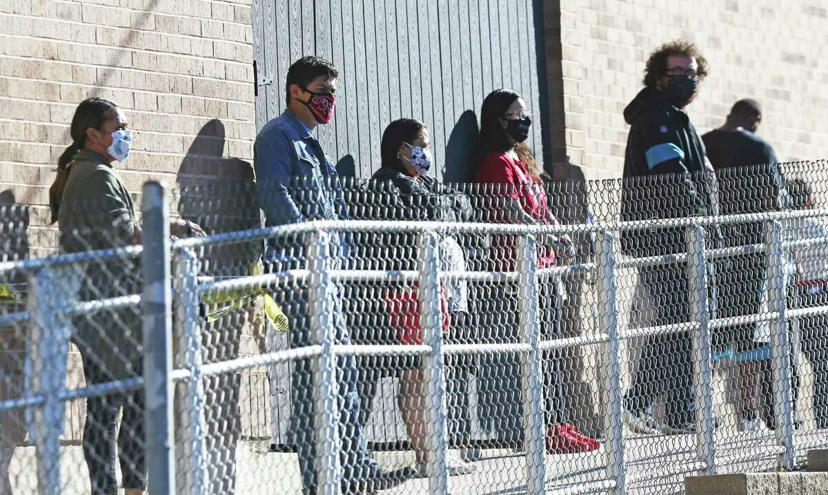 Everyone in line has a face covering at the Johnston Branch Library on Medina Base Road as voters wear masks while voting on the Southside on Oct. 28, 2020.