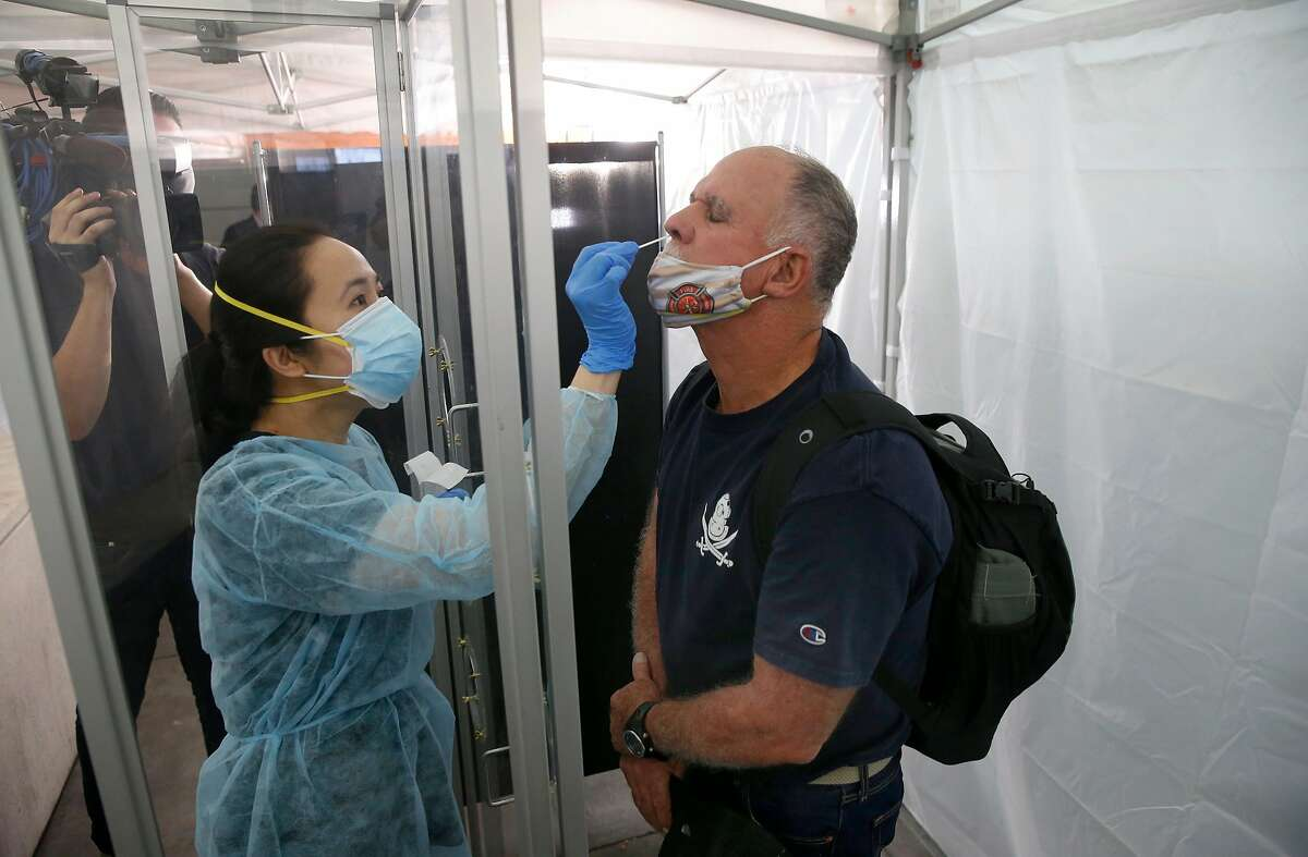 June Lopez, a medical technician with Go Health, collects a sample for a rapid coronavirus test from Jim Zoller at SFO in San Francisco, Calif. on Thursday, Oct. 15, 2020.