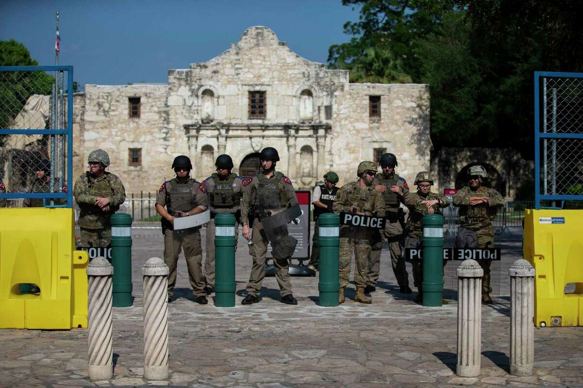 Texas state police and national guard personnel stand at the entrance to Alamo Plaza as protesters march nearby on June 9.