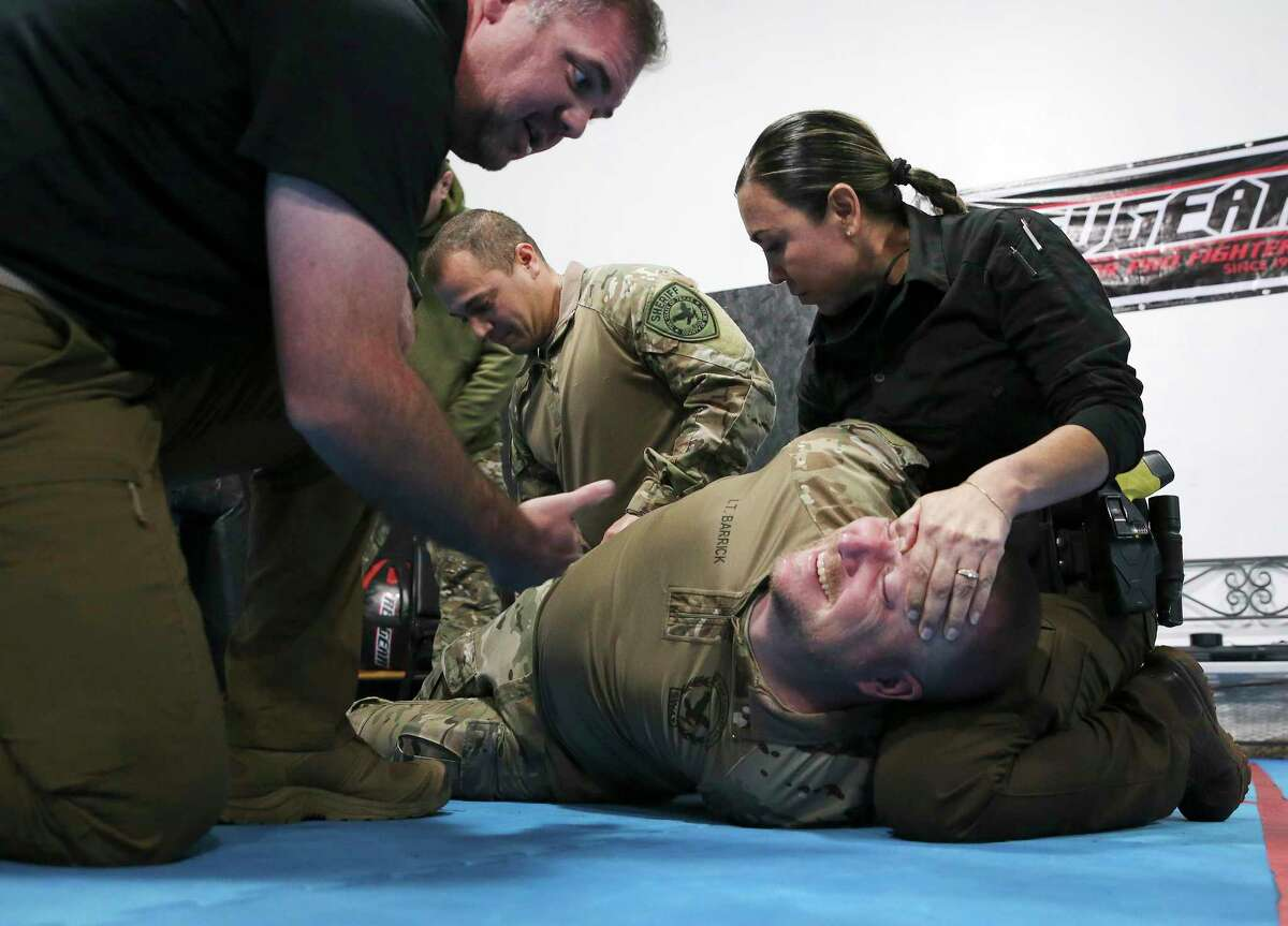 CALM Instructor Joshua Thomas, left, oversees Bexar County deputies as they practice a restraint technique during training.