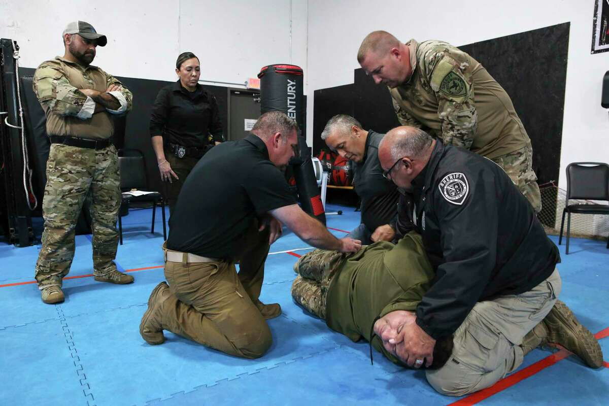 Instructor Joshua Thomas (left, kneeling) oversees Bexar County Sheriff's Office deputies as they practice a restraint technique during a training session discussing best practices for communication and active physical control when confronting individuals on Wednesday, Oct. 28, 2020. Con10gency Consultants held the all-day training session with a group of deputies at STW Krav Maga Self Defense & Training where they went over how best to detain an individual without jeopardizing either parties' safety and well-being. One exercise involved