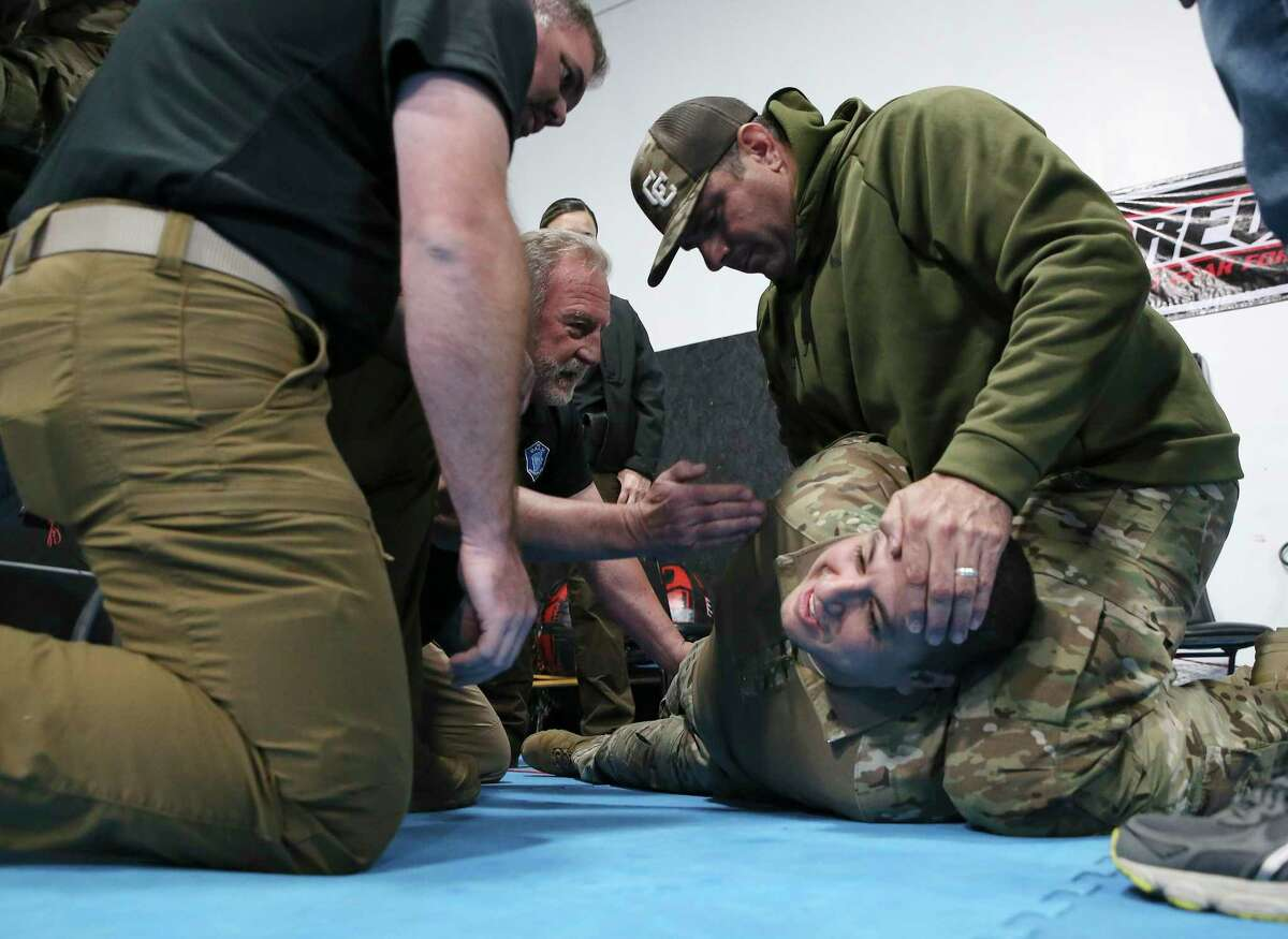 Instructor Joshua Thomas (from left) and Chief Instructor Pete Hardy oversee Bexar County Sheriff's Office deputies as they practice a restraint technique during a training session discussing best practices for communication and active physical control when confronting individuals on Wednesday, Oct. 28, 2020. Con10gency Consultants held the all-day training session with a group of deputies at STW Krav Maga Self Defense & Training where they went over how best to detain an individual without jeopardizing either parties' safety and well-being. One exercise involved