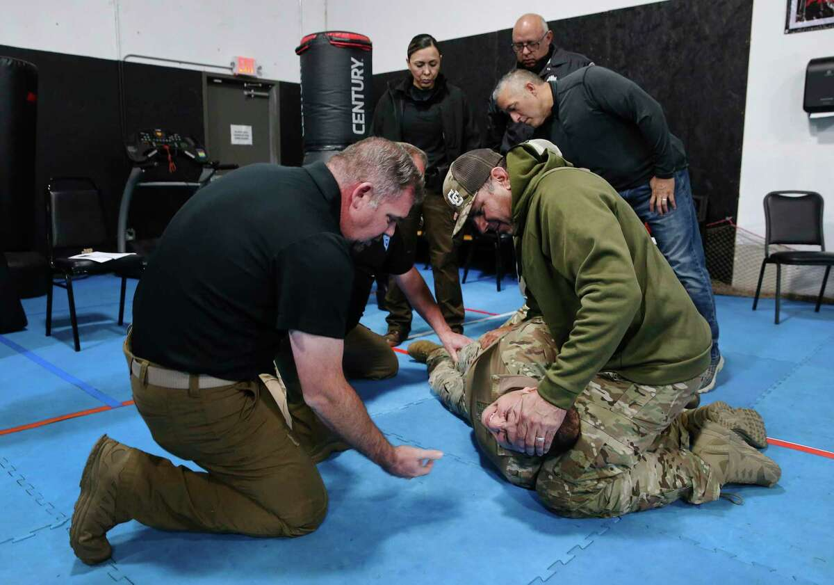 Instructor Joshua Thomas (left) oversees Bexar County Sheriff's Office deputies as they practice a restraint technique during a training session discussing best practices for communication and active physical control when confronting individuals on Wednesday, Oct. 28, 2020. Con10gency Consultants held the all-day training session with a group of deputies at STW Krav Maga Self Defense & Training where they went over how best to detain an individual without jeopardizing either parties' safety and well-being. One exercise involved