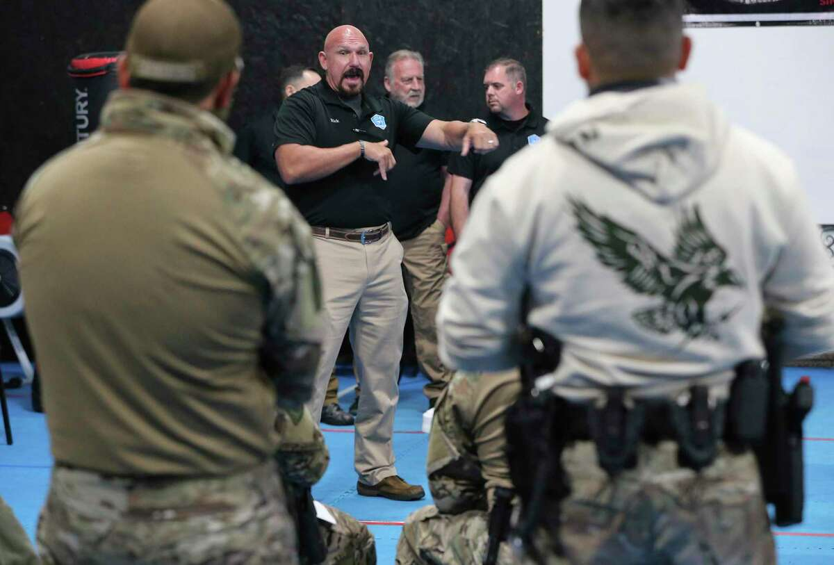 Consultant Richard Smith, center, lectures sheriff's deputies during a CALM training session.