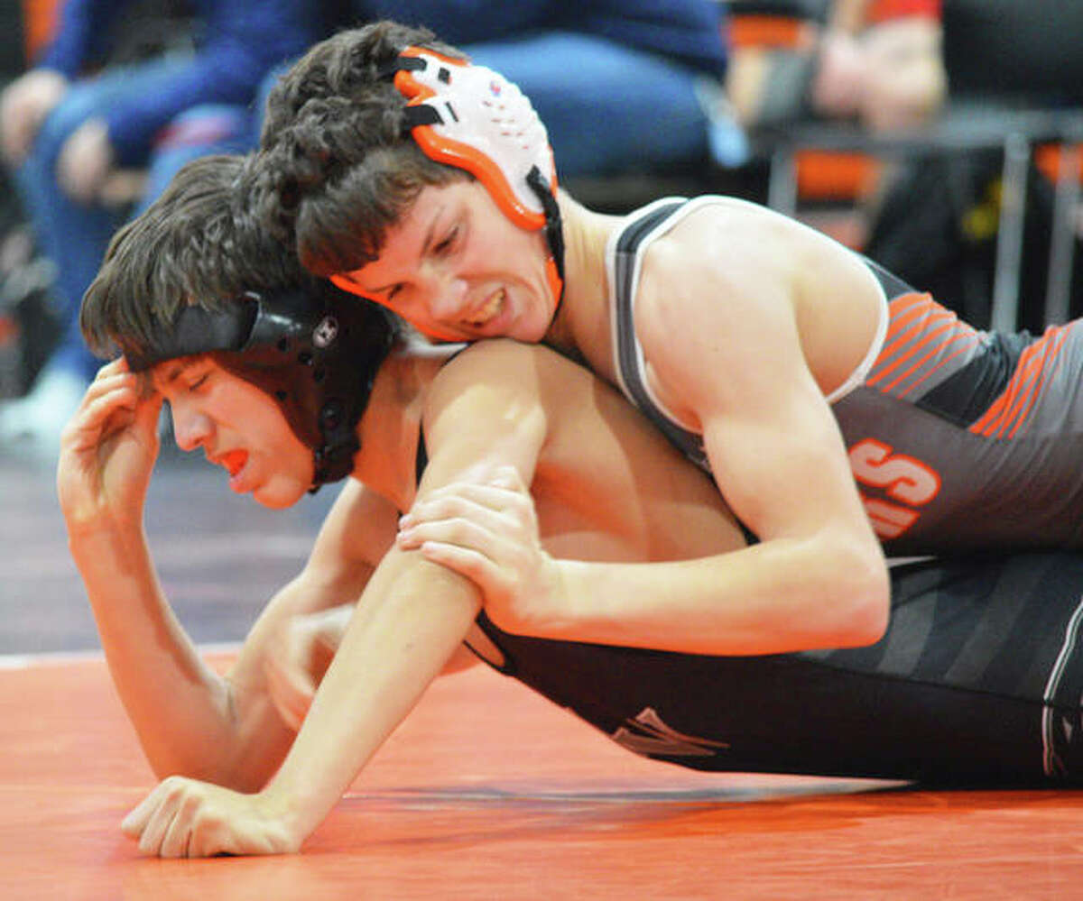 Edwardsville's Zeke Rhodes, top, takes control of his bout during a match last season.