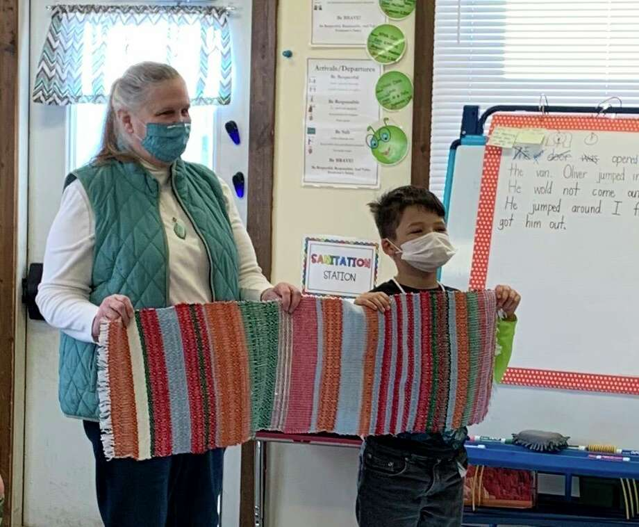 Lake County Historical Museum Curator Jill Engelman (left) presents Leon Burns from Big Jackson School, with the woven runner he helped create. (Submitted photo)