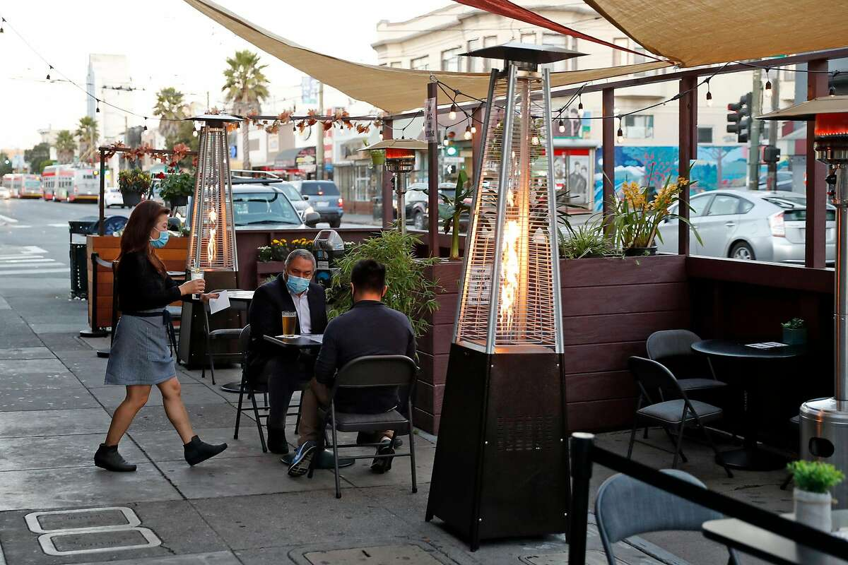 Bottoms Up Bar and Lounge owner Shirley Tan brings a drink to a diner at the parklet on Mission Street.
