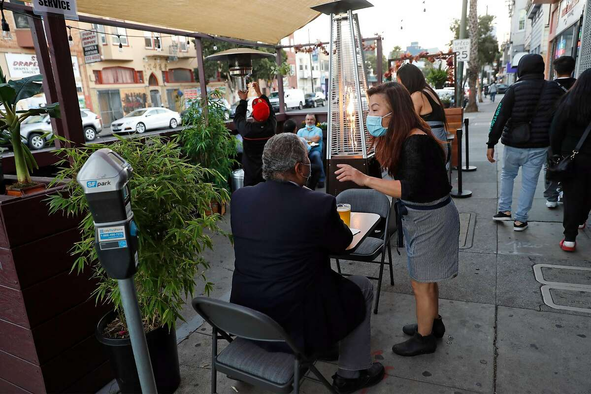 Bottoms Up Bar and Lounge owner Shirley Tan talks with a diner at the parklet on Mission Street.
