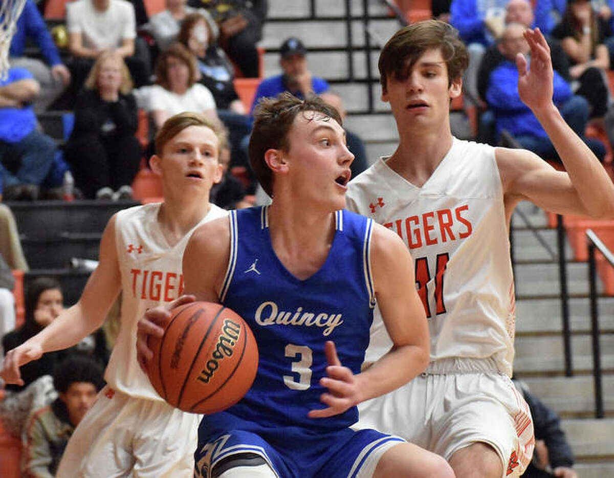 Edwardsville's Brennan Weller, right, and Preston Weaver, left, guard Quincy's Logan Reis in the third quarter of the Class 4A Edwardsville Regional semifinals in March.