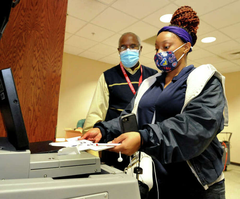 Senior Bianca Woods of Rockford, front, is assisted by Election Judge Herb Clay as she places her ballot in to the tabulator during early voting at SIUE Wednesday. Early voting on campus will continue through Friday, from 10 a.m. to 5 p.m., in the Willow Room at the Morris University Center. Election Day is Tuesday. Photo: Thomas Turney | For The Intelligencer