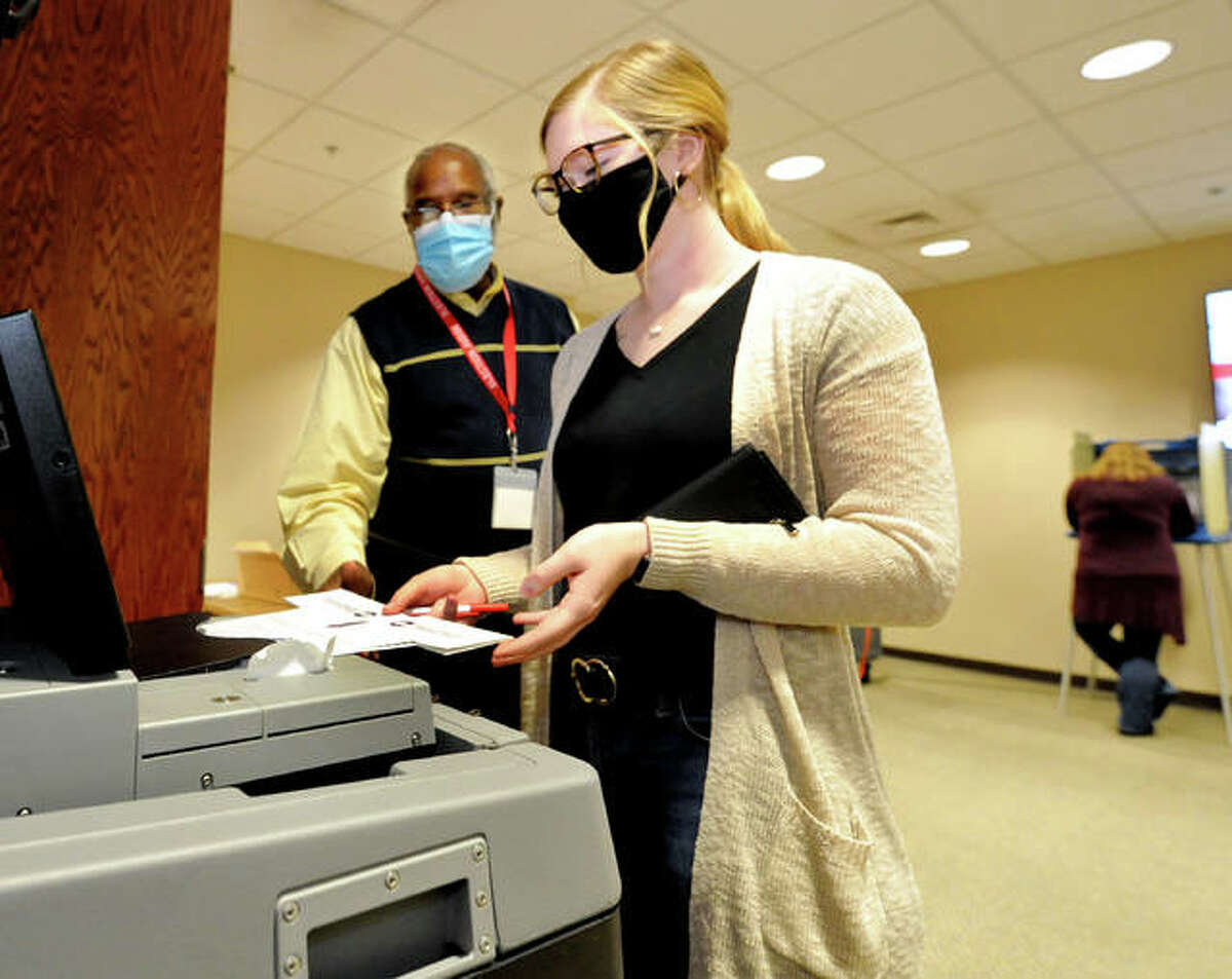 SIUE junior Maggie Hass of East Alton, front, is assisted by Election Judge Herb Clay as she places her ballot into the machine during early voting at SIUE Wednesday.