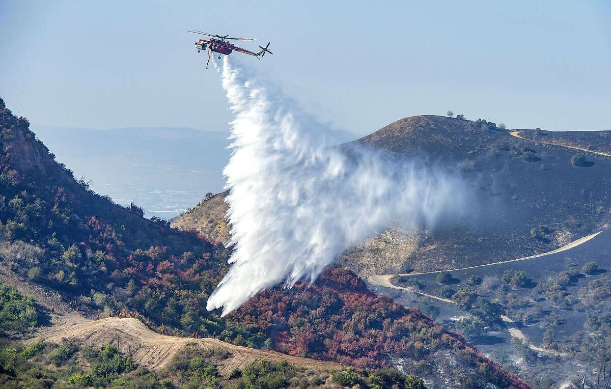 With hand crews on the ground at bottom left, a helicopter drops water onto hot spots from the Silverado Fire off Santiago Canyon Road in Whiting Ranch Wilderness Park on Wednesday, Oct. 28, 2020, near Lake Forest, Calif. Dangerous winds have subsided and humidity is rising in the Bay Area, but fire risk remains with little chance of rain over the next week.