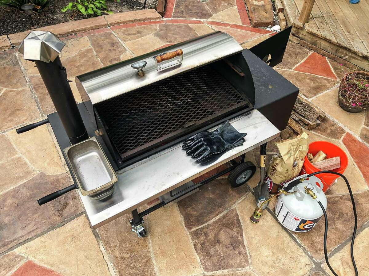 A typical backyard smoker setup includes offset barrel smoker, log lighter, mini-shovel for managing the fire, wood chips and charcoal for kindling, water pan, BBQ gloves, wood logs for burning.