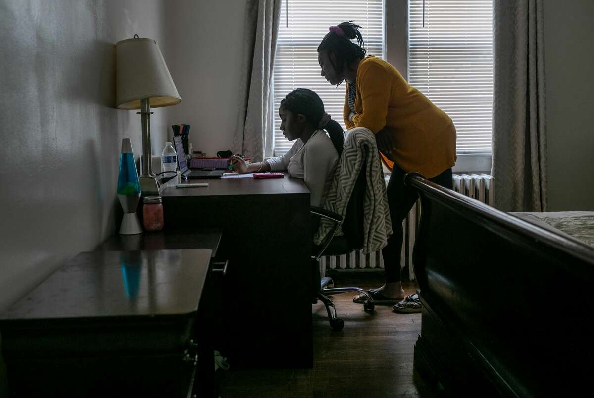 Abigail Previlon, 13, takes part in remote distance learning on a Chromebook with the help of her mother Carlene at home on October 28, 2020 in Stamford, Connecticut.