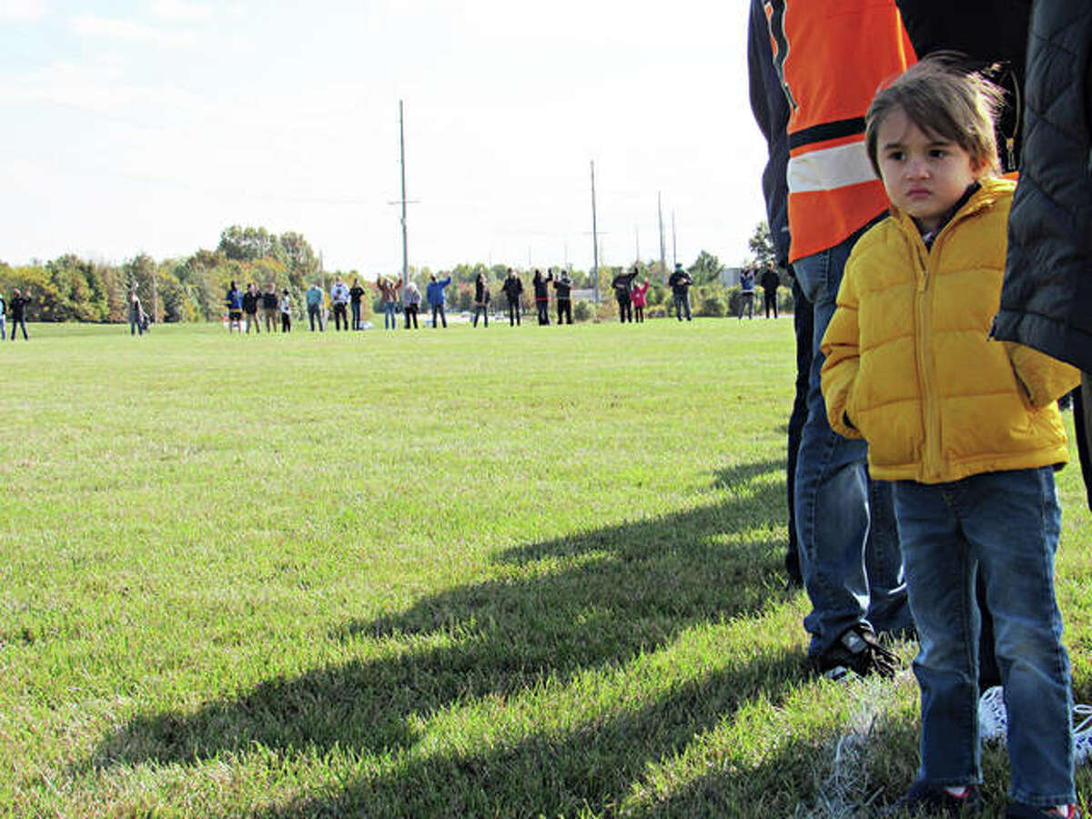 A youngster takes his spot on the field at the site of the proposed community-centered facility called TheCENTER near Tiger Drive and Governors' Parkway during an open house Saturday in Edwardsville. The child attended the event with Edwardsville resident Cindy Akeman, who has one son currently playing EHS hockey and one who is a former Tiger. Attendees were asked to stand in formation to outline the circumference of the proposed facility after hearing brief speeches from city officials as well as former professional hockey player and commentator, Kelly Chase. An advocate for the proposed project, Chase said the facility is about more than just sports but bringing people together, especially youth.