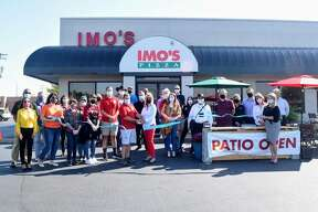 Lori Bromberg owner of Imo's pizza and is featured in the center.