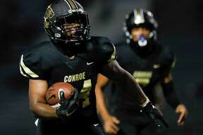 Conroe running back Jordan O'Neal (34) runs for a 25-yard touchdown during the second quarter of a non-district high school football game at Buddy Moorhead Stadium, Friday, Oct. 2, 2020, in Conroe.