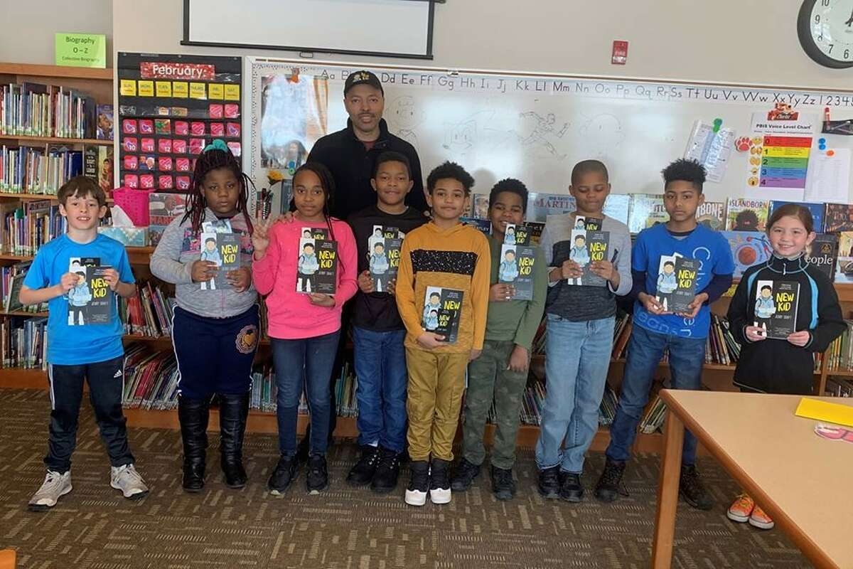 Students at New Scotland Elementary School with author and illustrator Jerry Craft, holding their copies of his book,