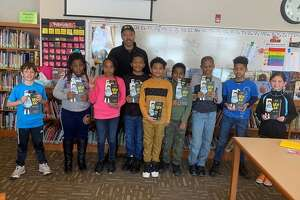 """Students at New Scotland Elementary School with author and illustrator Jerry Craft, holding their copies of his book, """"New Kid,"""" funded by a grant from the Albany Fund for Education."""