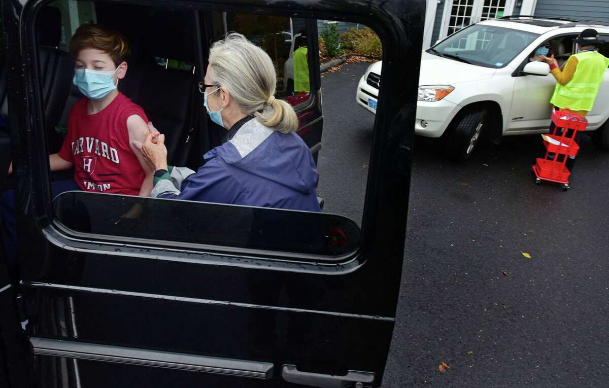 Julius Tangorra, 9, receives a jab from nurse Laura Wood at the drive-thru flu shot clinic provided by Visiting Nurse & Hospice of Fairfield County on Oct. 28.