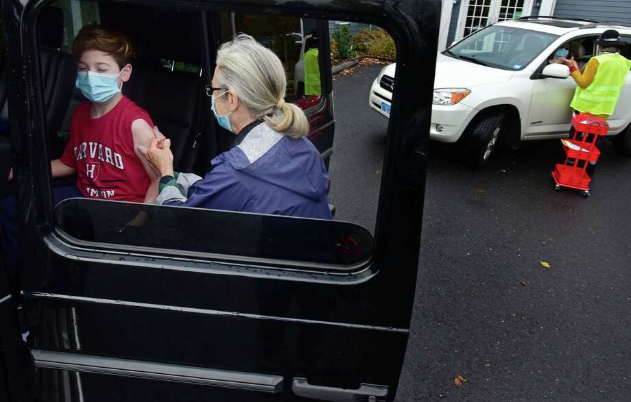 Julius Tangorra, 9, receives a jab from nurse Laura Wood at the drive-thru flu shot clinic provided by Visiting Nurse & Hospice of Fairfield County on Oct. 28. Photo: Erik Trautmann / Hearst Connecticut Media / Norwalk Hour