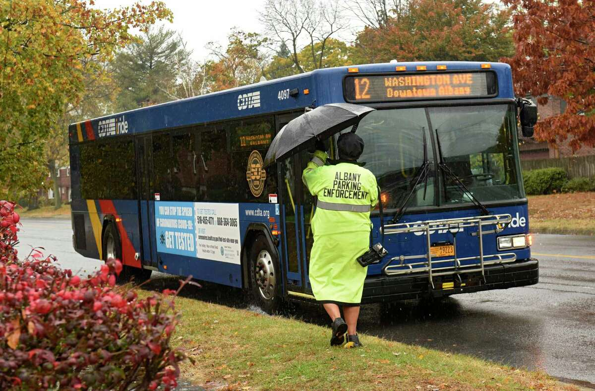 An Albany Parking Enforcement worker starts to fold up her umbrella as she boards a CDTA bus during a rainfall on Thursday, Oct. 29, 2020 in Albany, N.Y. CDTA will be busing voters from the city of Albany to their polling place on Everett Road on Tuesday after the polling place had to be moved from a Catholic school. (Lori Van Buren/Times Union)