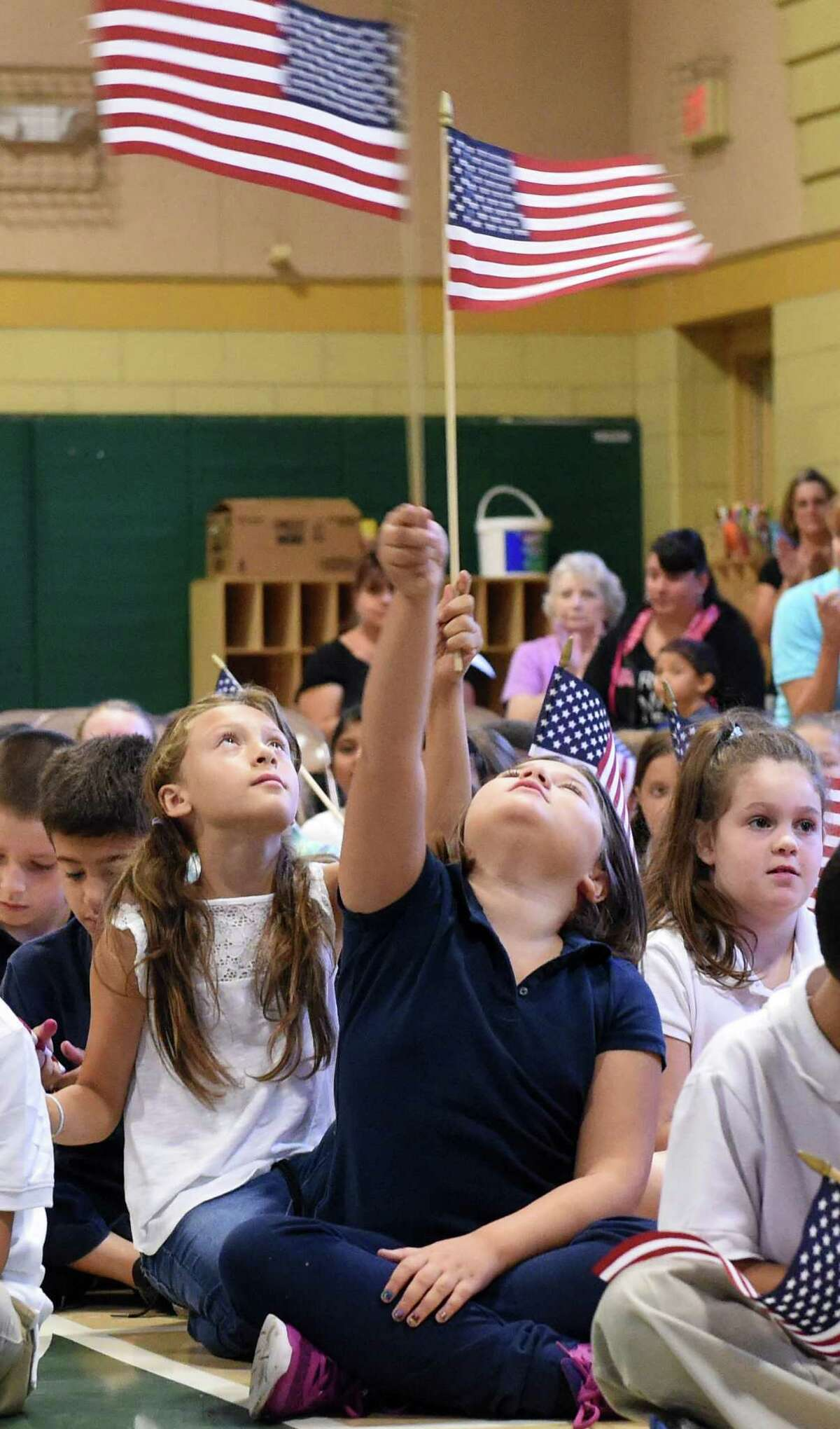 (Peter Hvizdak - New Haven Register) Two elementary school students raise the U.S. flag high during a during a We Love America Day school assembly honoring the memory of the heroes of the 9/11 in the gym at the Grove J. Tuttle Elementary School in East Haven, Connecticut Friday, September 11, 2015 marking the anniversary of the 9/11 attacks on the United States in 2001.