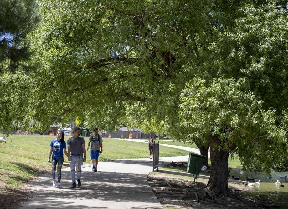 Walkers stroll around Wadley Barron Park on June 6, 2019. Studies have shown that residents are happy with their city if they have opportunities for chance encounters – such as might occur at a local park. Photo: Jacy Lewis/191 News