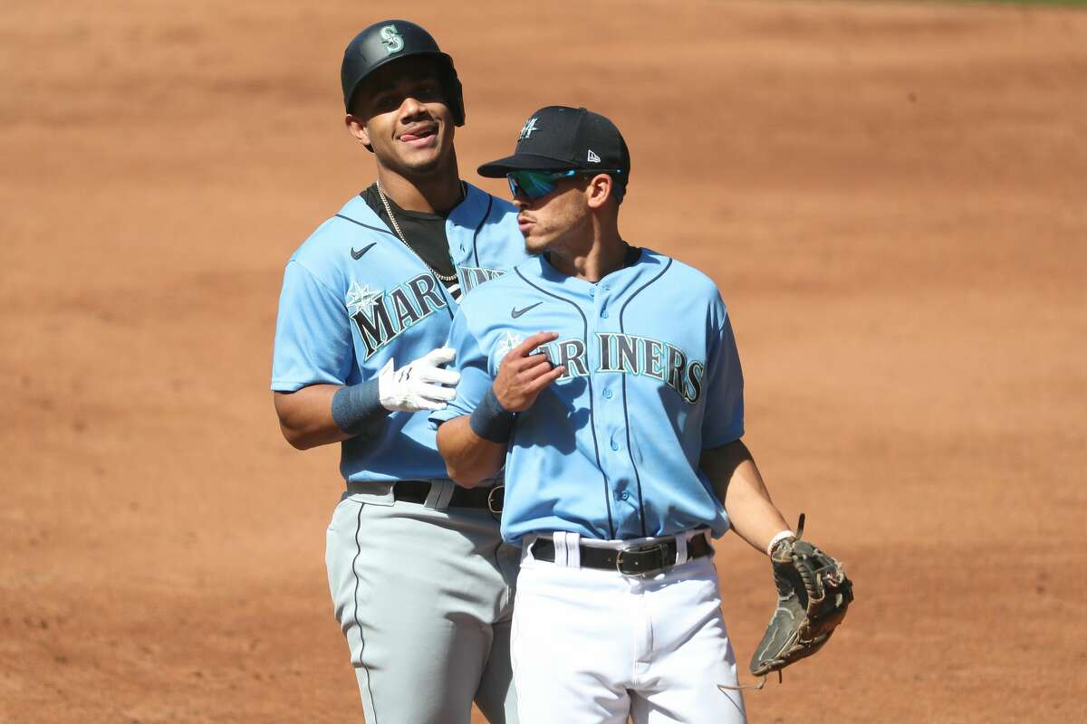 SEATTLE, WASHINGTON - JULY 14: Julio Rodriguez #80 (L) and Sam Haggerty #28 of the Seattle Mariners interact in the third inning of an intrasquad game during summer workouts at T-Mobile Park on July 14, 2020 in Seattle, Washington. (Photo by Abbie Parr/Getty Images)
