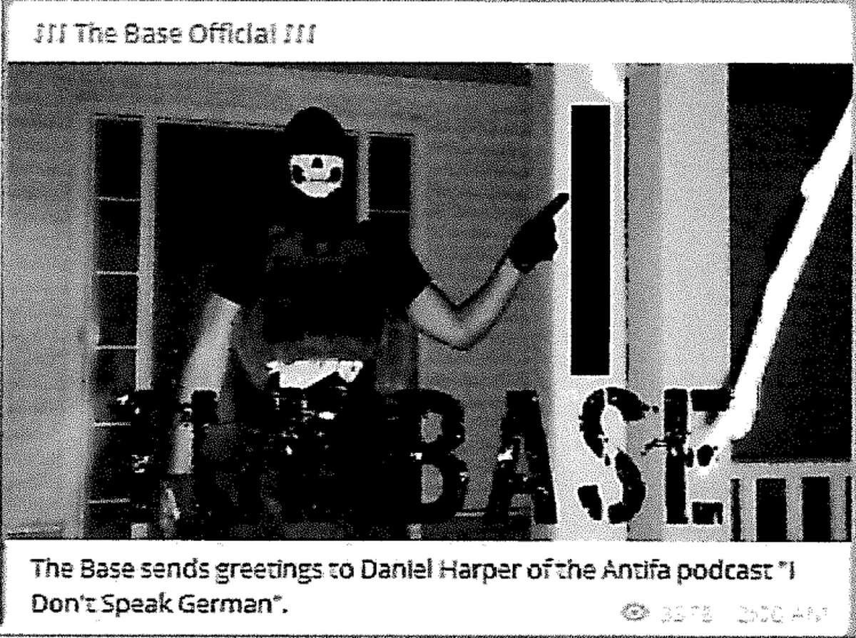 """A screen shot of an arrest affidavit shows a photograph that was uploaded to """"The Base"""" channel on the publicly available social media platform Telegram. According to the affidavit, the photograph shows Justen Watkins, 25, of Bad Axe, wearing a black skull mask, a Totenkopf shirt, camouflage pants, and a tactical plate carrier with rifle magazines that has a patch of the logo for """"The Base"""" visible on the front of the vest."""