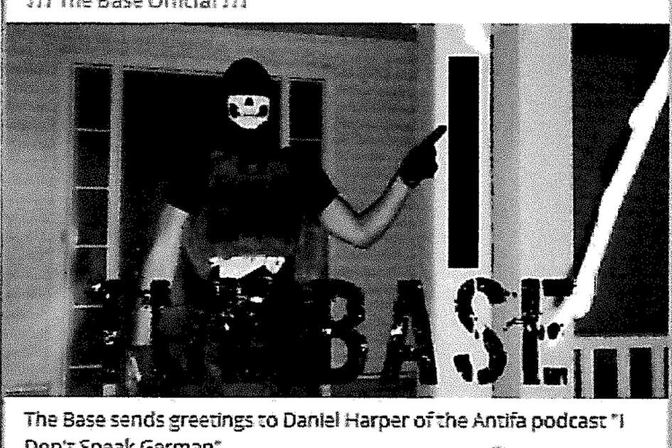 "A screen shot of an arrest affidavit shows a photograph that was uploaded to ""The Base"" channel on the publicly available social media platform Telegram. According to the affidavit, the photograph shows Justen Watkins, 25, of Bad Axe, wearing a black skull mask, a Totenkopf shirt, camouflage pants, and a tactical plate carrier with rifle magazines that has a patch of the logo for ""The Base"" visible on the front of the vest."