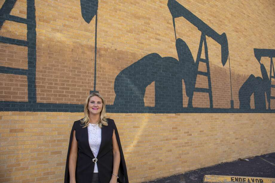 Amy Hall, an account manager at Seven Lakes Technology, poses Oct. 2 in front of pump jack art at the corner of Big Spring Street and Illinois Avenue. She said she has been mentored by longtime industry professionals. Photo: Jacy Lewis/Reporter-Telegram / MRT