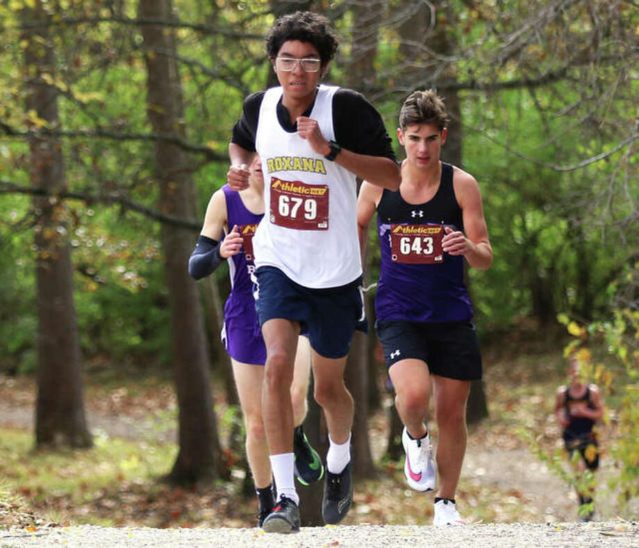 Roxana senior Carlos Ruvalcaba (front) leads runners out of the woods at Loveless Park during the Carlinville Class 1A Regional last Saturday. Ruvalcaba placed second in the race and joins his Shells teammates Saturday in the Decatur St. Teresa Sectional at Hickory Point golf course in Forsyth. Photo: Greg Shashack / The Telegraph