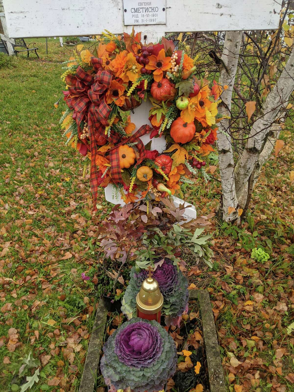 Many graves in Jordanville's Russian Orthodox cemetery were decorated with autumn adornments like purple winter cabbage, red and orange leaves, even pumpkins and gourds.