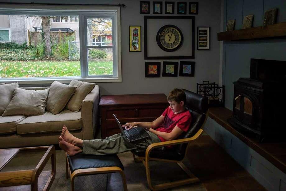 Sean Surbrook, 14, works on schoolwork Thursday morning at home in Midland. (Katy Kildee/kkildee@mdn.net)