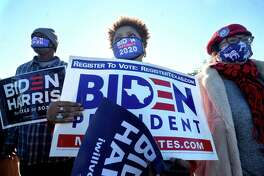 Clarissa Provost (center) takes in the speakers' messages as she joins in the Biden/Harris bus rally in Beaumont early Thursday morning. Several joined the caravan following the bus for a rally stop in Port Arthur. Photo taken Thursday, October 29, 2020 Kim Brent/The Enterprise